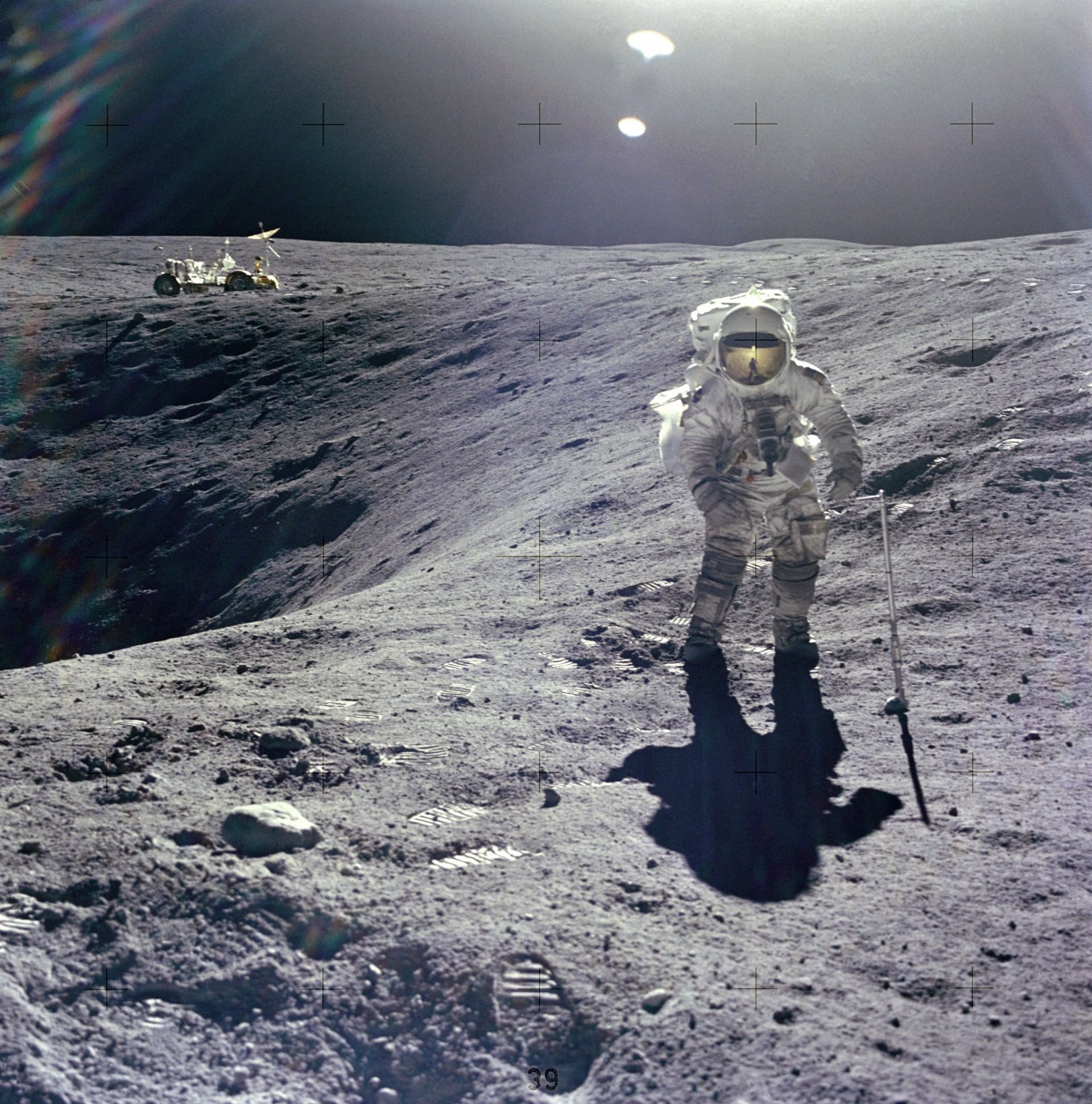 Astronaut Duke on the lunar surface at the edge of a crater